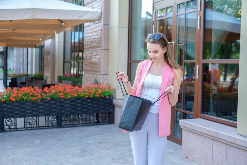 Hållande shoppingpåse för härlig kvinna och le - utomhus arkivfoto