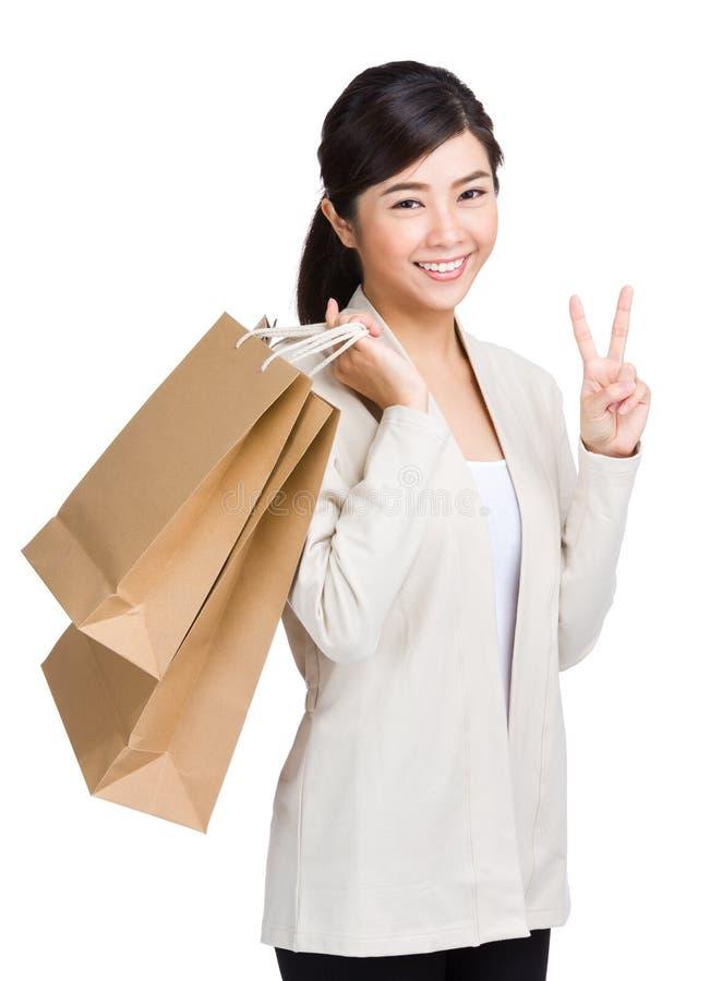 Hållande shoppingpåse för kvinna och ge segertecknet arkivfoton