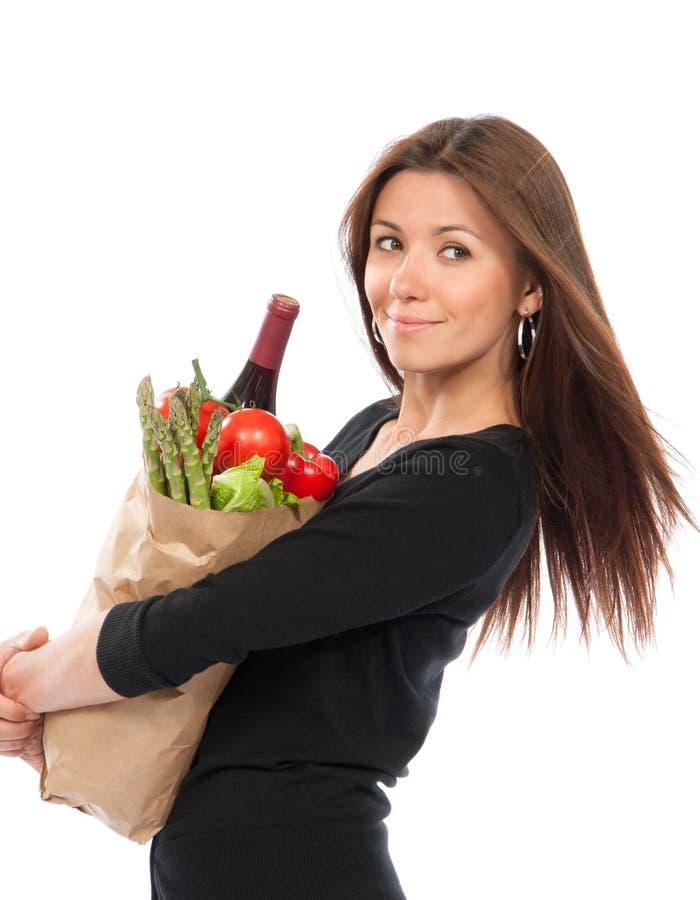 Hållande shoppingpåse för ung kvinna med livsmedelgrönsaker royaltyfria foton