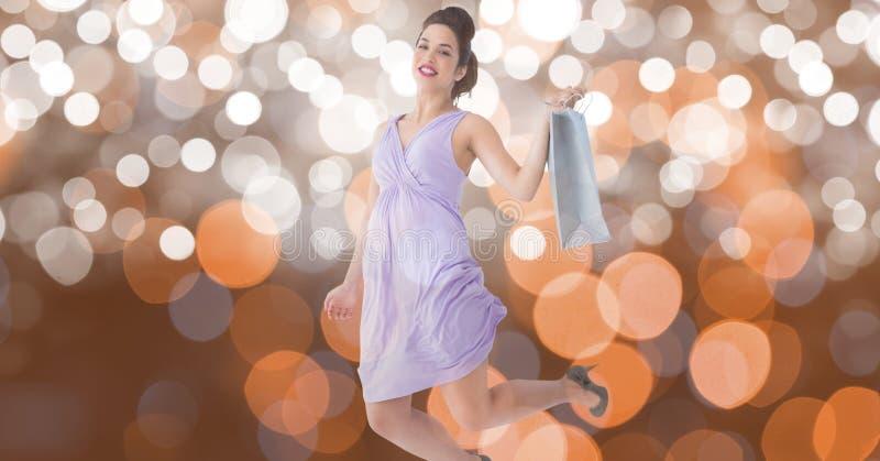 Hållande shoppingpåse för upphetsad kvinna, medan hoppa över bokeh royaltyfri fotografi