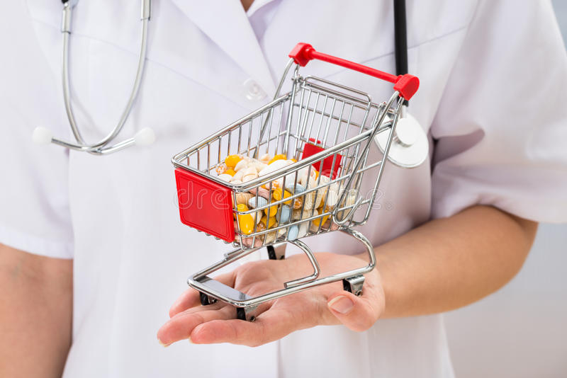 Hållande shoppingvagn för doktor med preventivpillerar arkivbild