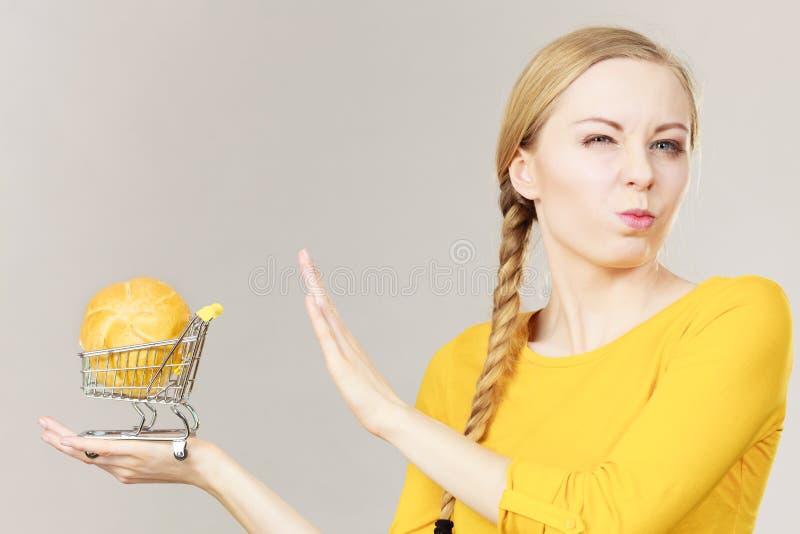 Hållande shoppingvagn för kvinna med bröd royaltyfria foton