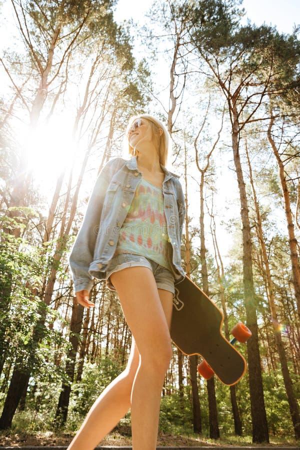 Hållande skateboard för nätt kvinna utomhus åt sidan se royaltyfria foton