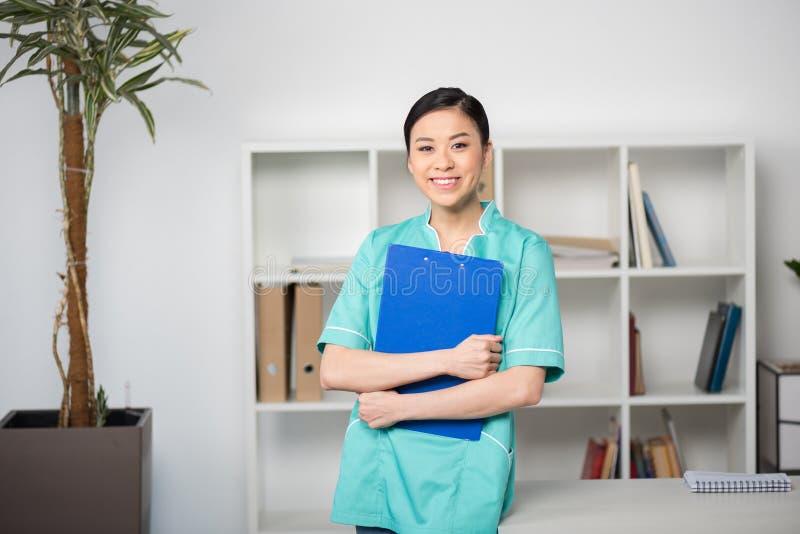 Hållande skrivplatta för asiatisk internist med diagnos och se kameran arkivfoton
