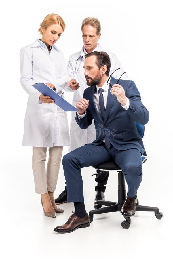 hållande skrivplatta för doktorer och peka med fingret medan chockad affärsman som ser det medicinska dokumentet arkivbilder