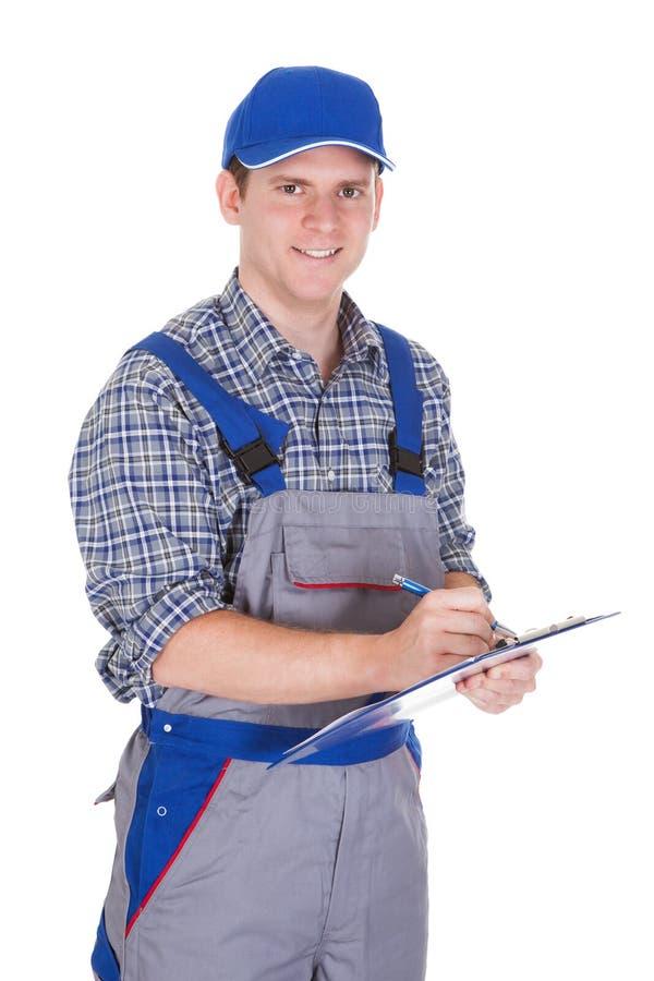 Hållande skrivplatta för manlig byggnadsarbetare royaltyfri bild