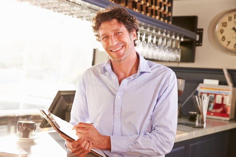 Hållande skrivplatta för manlig restaurangchef, stående royaltyfria bilder