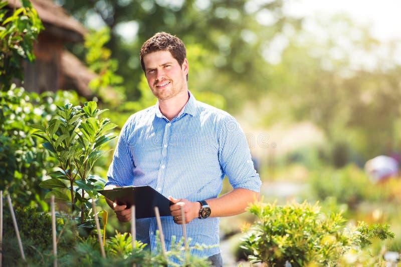 Hållande skrivplatta för trädgårdsmästare, i hans trädgård, solig natur för gräsplan arkivbild