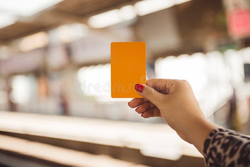 Hållande smartcard för kvinnahand för mrt eller drev på suddigt av traien royaltyfri foto