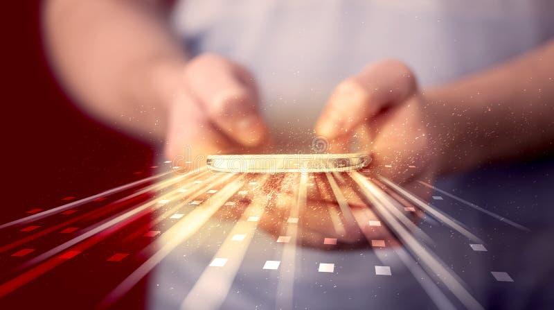 Hållande smarthphone för person med teknologiljusapplikationer royaltyfri bild