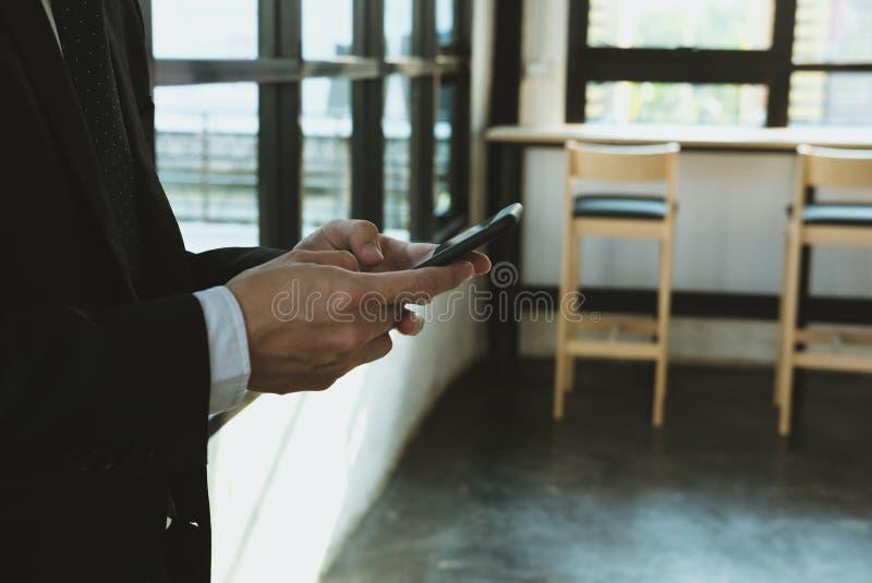 Hållande smartphone för affärsman & användaapp på kontoret mantextin arkivbilder