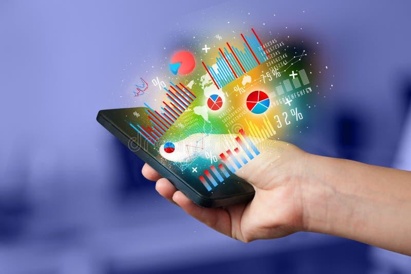 Hållande smartphone för affärsman med diagramsymboler royaltyfri foto