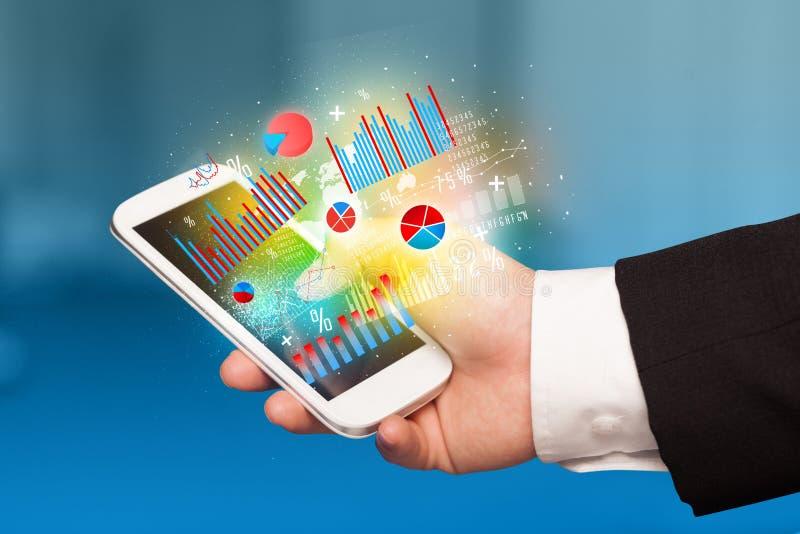 Hållande smartphone för affärsman med diagramsymboler arkivbild