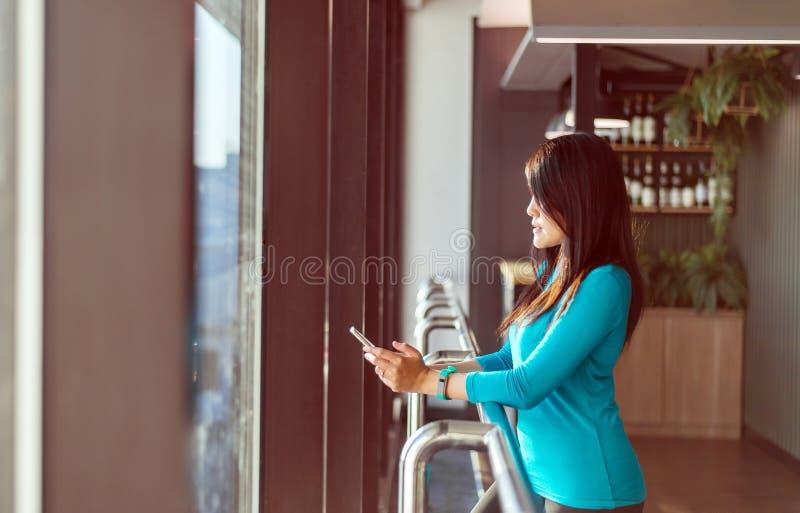 Hållande smartphone för asiatisk kvinnapassagerare och kontrollerande flyg- eller online-incheckning- och loppstadsplanerare på d royaltyfria bilder