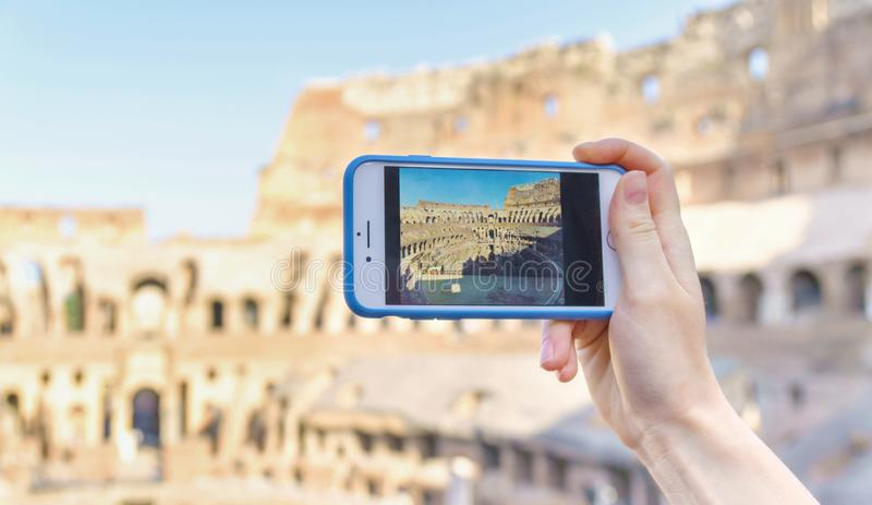 Hållande smartphone för flicka med bilden av Colosseo italy rome arkivbild