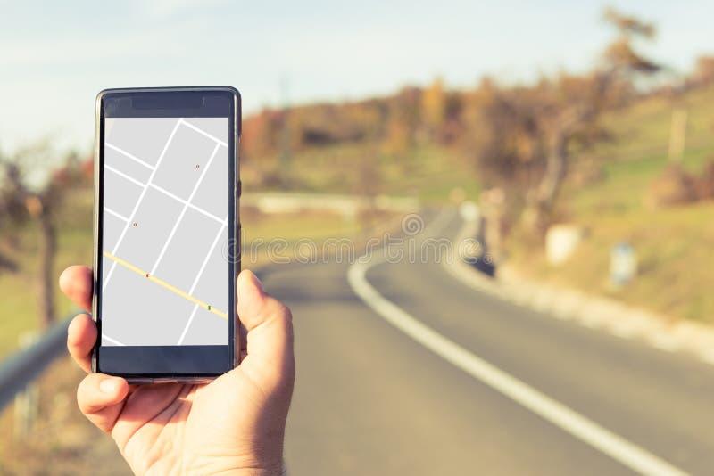 Hållande smartphone för hand med gps-översikten på utomhus- backgroun för höst arkivbild