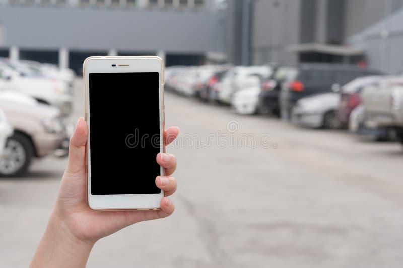 Hållande smartphone för kvinnahand i bilparkeringsområde royaltyfria foton