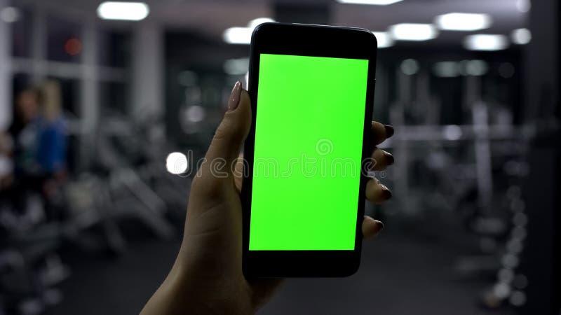 Hållande smartphone för kvinnlig hand i idrottshallen, grön skärm, online-konditionapplikation royaltyfria foton