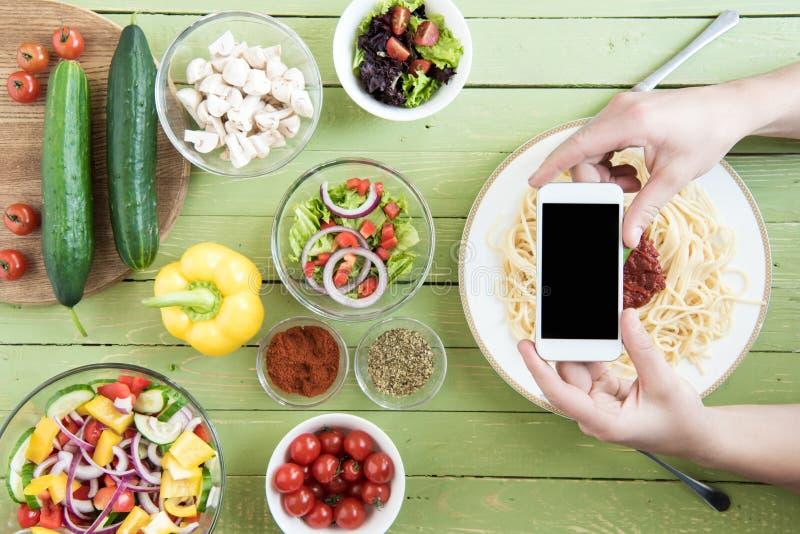 Hållande smartphone för person med den tomma skärmen och nya grönsaker för fotografera spagetti och på trätabellen royaltyfri bild