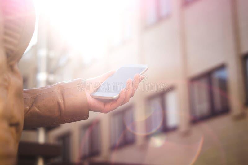 Hållande smartphone för stads- kvinna och gå i solsken Modern och moderiktig livsstil Soluppgång eller solnedgång i stadsmitten arkivfoto