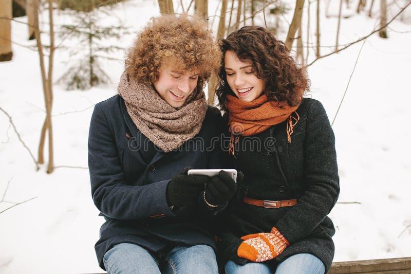 Hållande smartphonesammanträde för par utomhus i vinter royaltyfri bild