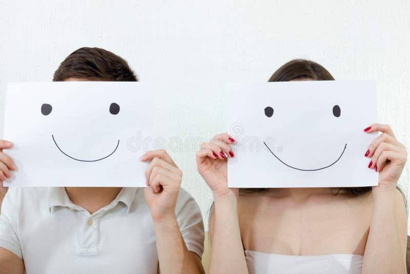 Hållande smileys för lyckliga par över deras framsidor arkivbild