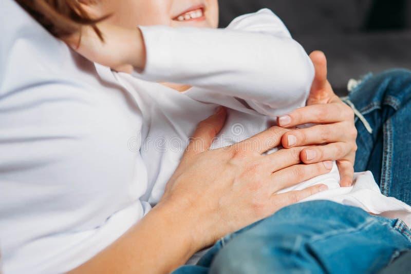 Hållande son för oigenkännlig moder i henne nära övre händer för armar arkivfoto