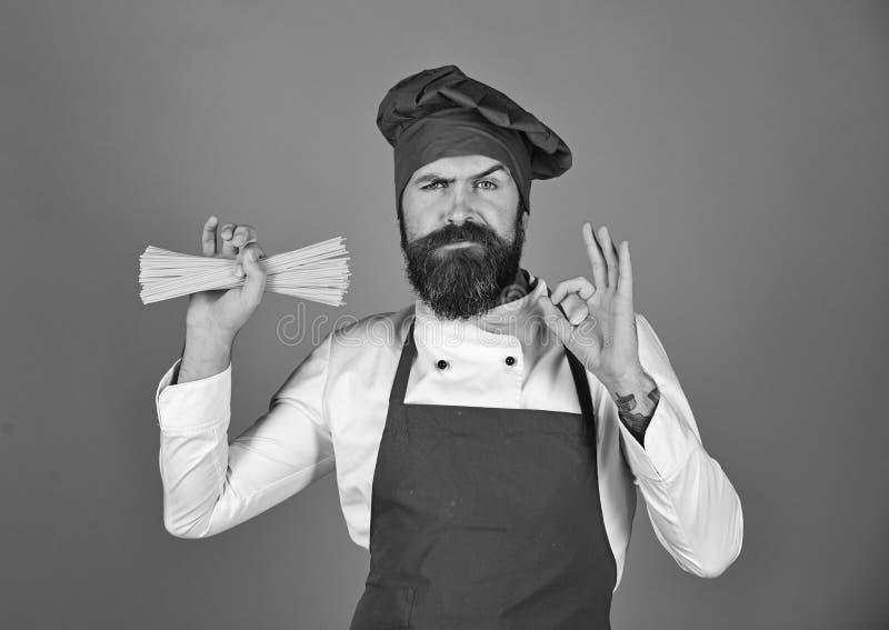 Hållande spagetti för kock i hans ok tecken för hand och för visning arkivbilder