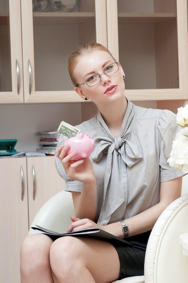Hållande spargris för affärskvinna som innehåller en dollar royaltyfria bilder