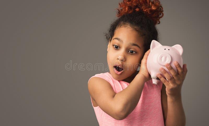 Hållande spargris för gullig liten svart flicka royaltyfri bild