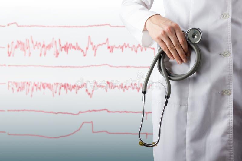 Hållande stetoskop för kvinnliga doktors hand på suddiga läkarundersökningblått royaltyfri foto