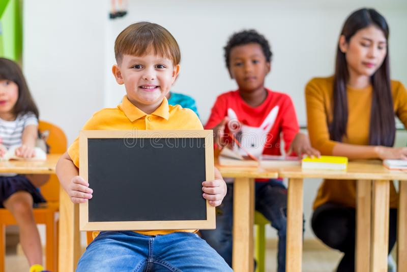 Hållande svart tavla för ungepojke med tillbaka till skolaordet med diversi royaltyfri bild