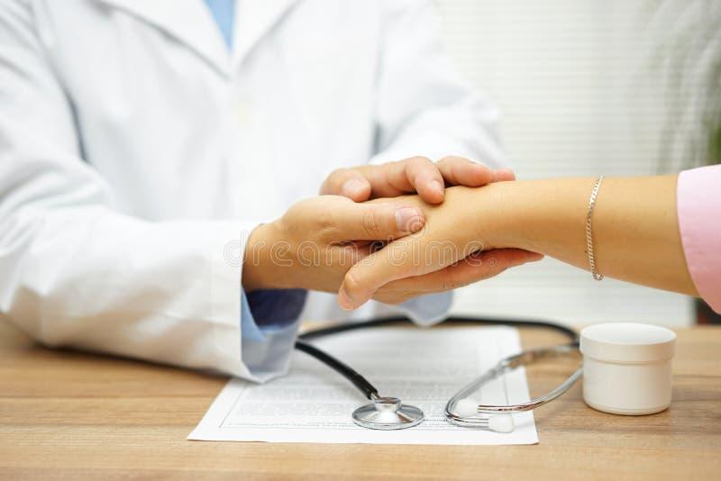 Hållande tålmodig hand för doktor med medkänsla och komfort royaltyfri foto