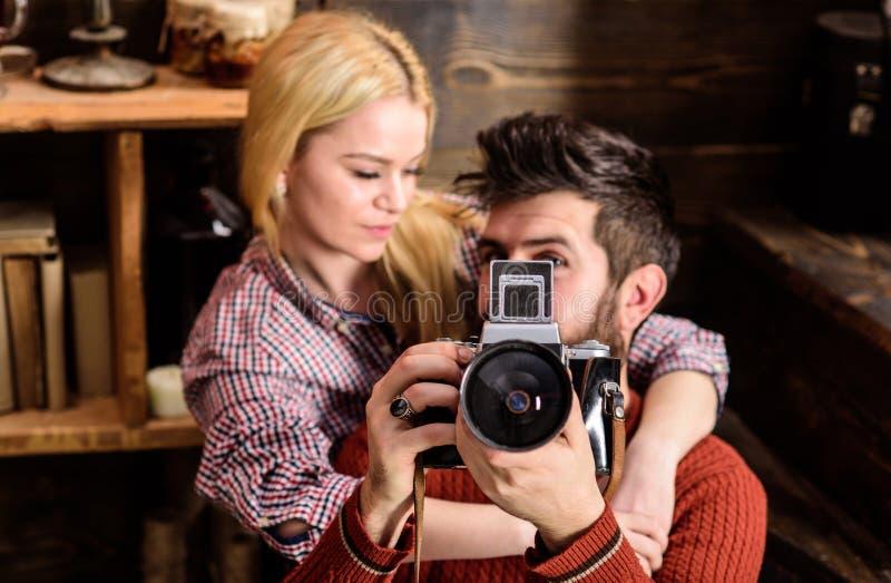 Hållande tappningkamera för Hipster, medan flickvännen kramar honom Tappningfotografbegrepp Förälskade par spenderar romantiker royaltyfria foton
