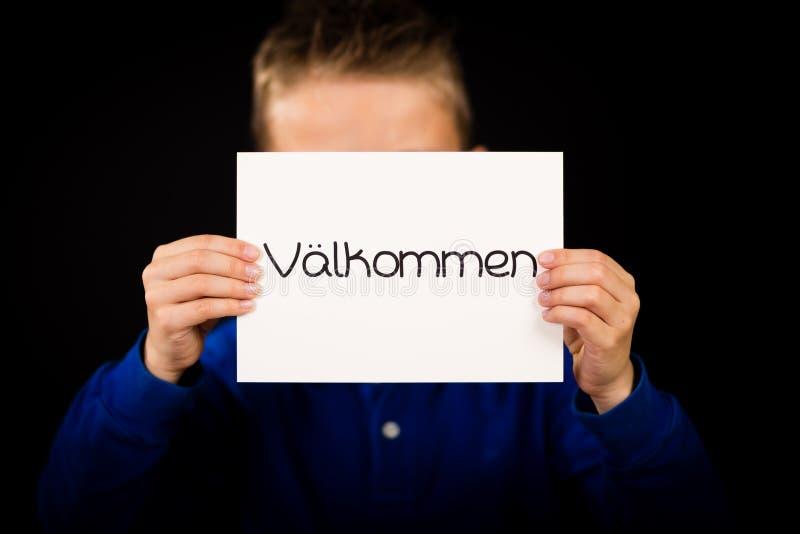 Hållande tecken för barn med svenskordet Valkommen - välkomnande arkivfoton