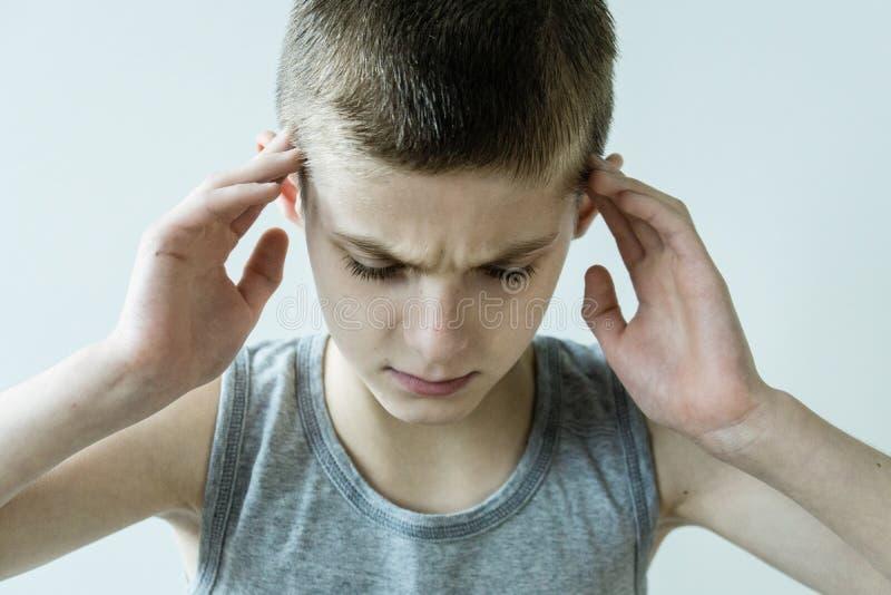 Hållande tempel för stressad ung pojke med händer arkivfoton