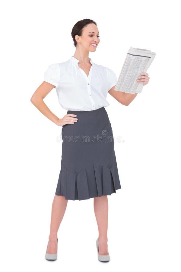 Hållande tidning för gladlynt stilfull affärskvinna royaltyfri foto
