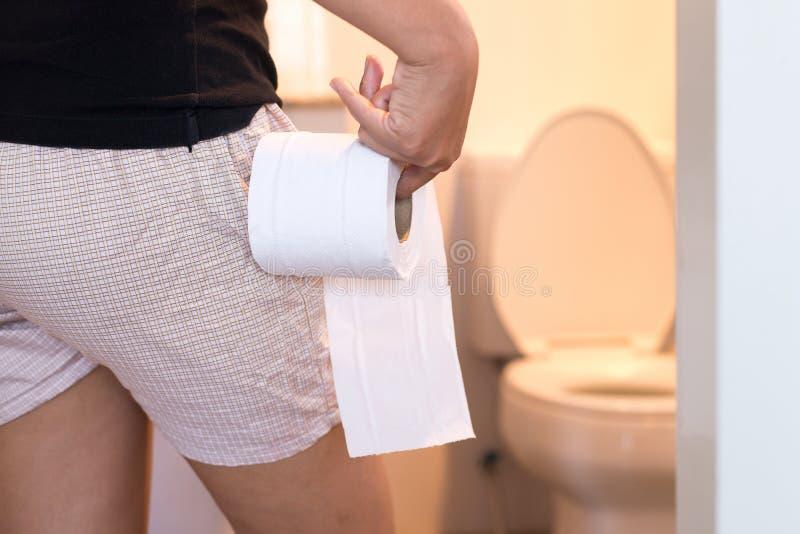 Hållande toalettpapper för kvinna och användabadrum i morgon royaltyfri fotografi