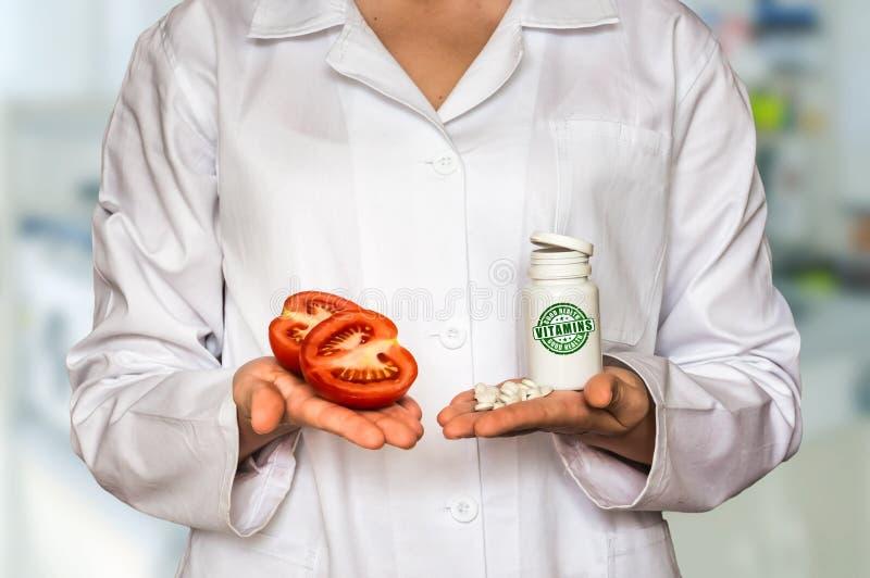 Hållande tomat för barndoktor och flaska av preventivpillerar med vitaminer royaltyfri foto