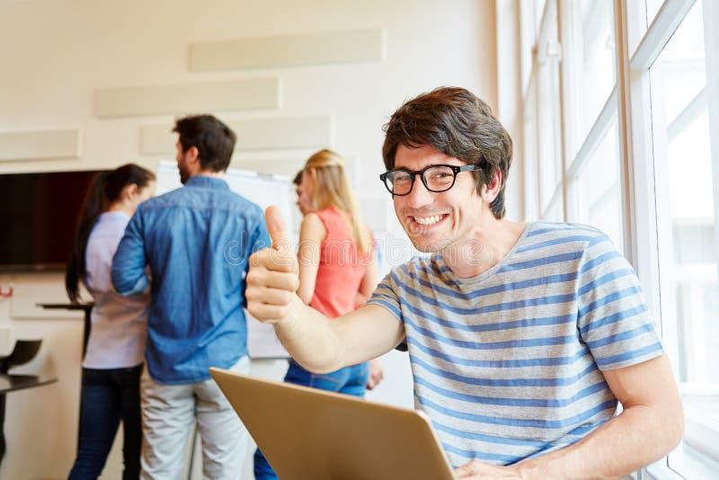 Hållande tummar för Nerdstudent upp arkivfoton