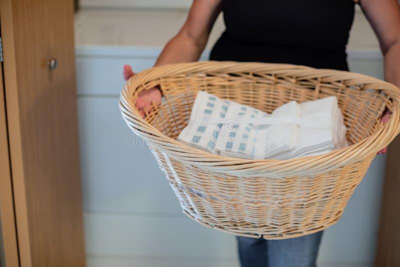 Hållande tvättkorg för kvinna av nya rena handdukar royaltyfri foto