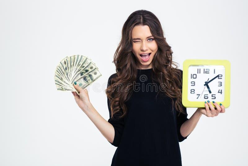 Hållande väggklocka för lycklig flicka med räkningar av dollaren royaltyfri foto