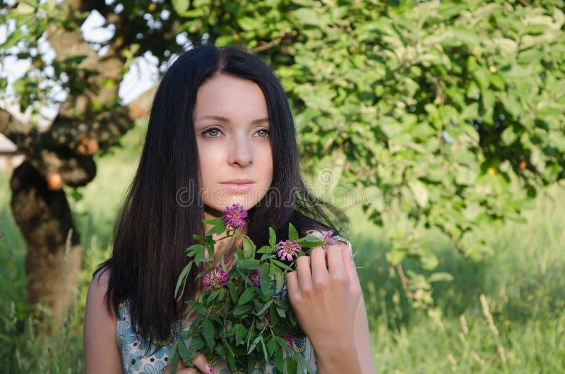 Hållande växt av släktet Trifoliumbukett för ung flicka arkivfoto