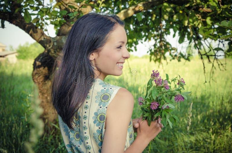 Hållande växt av släktet Trifoliumbukett för ung flicka royaltyfria bilder