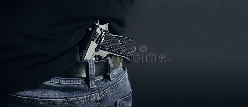 Hållande vapen för terroristtjuvman i hans hand Gömd tryckspruta Isolerat på mörk bakgrund kopiera avstånd fotografering för bildbyråer