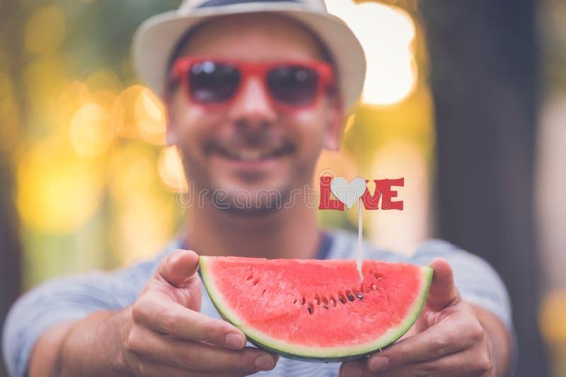 Hållande vattenmelon för man med förälskelsetecknet fotografering för bildbyråer