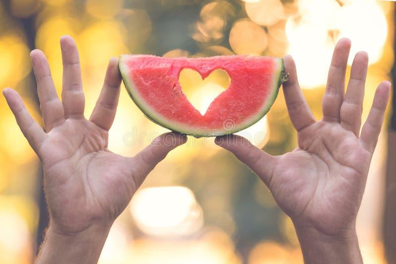 Hållande vattenmelonskiva för man utomhus arkivfoto