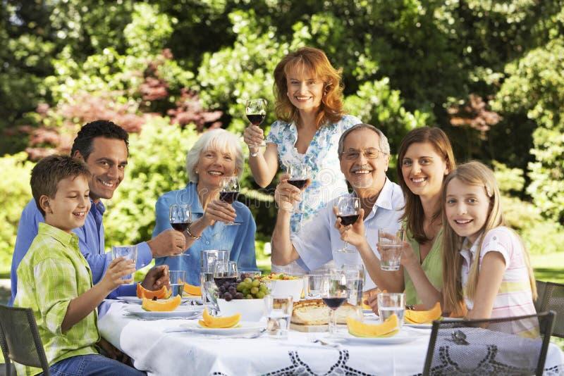 Hållande vinexponeringsglas för familj på tabellen i bakgård arkivfoto