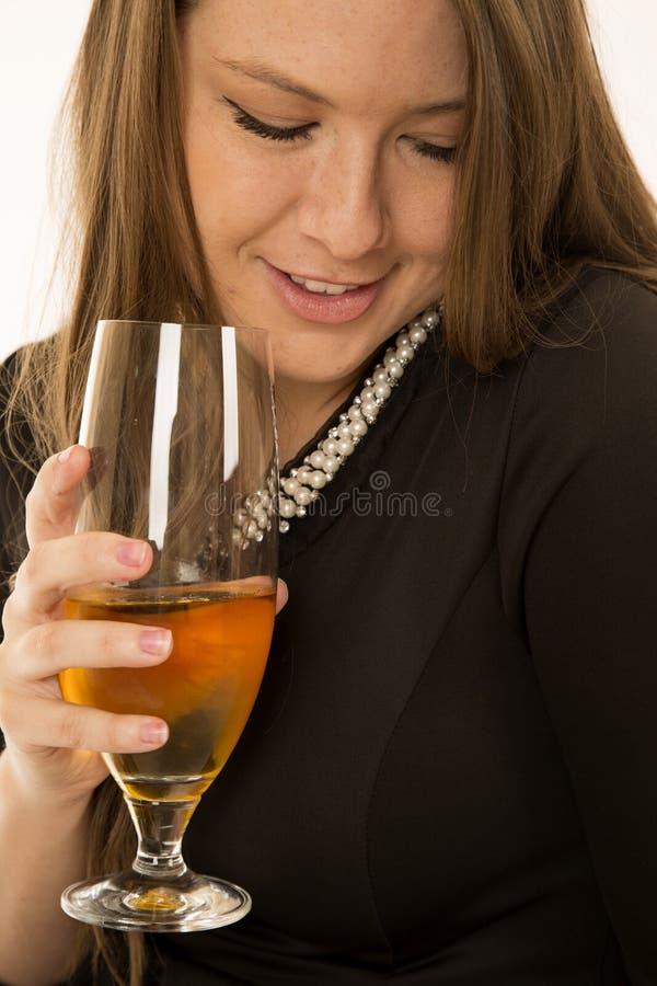 Hållande vinexponeringsglas för kvinna och se ner att le arkivbilder