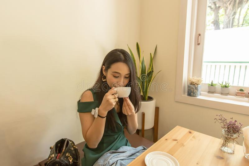 Hållande vit kopp för asiatisk kvinna och dricka ett varmt kaffe eller te i kafé royaltyfria foton